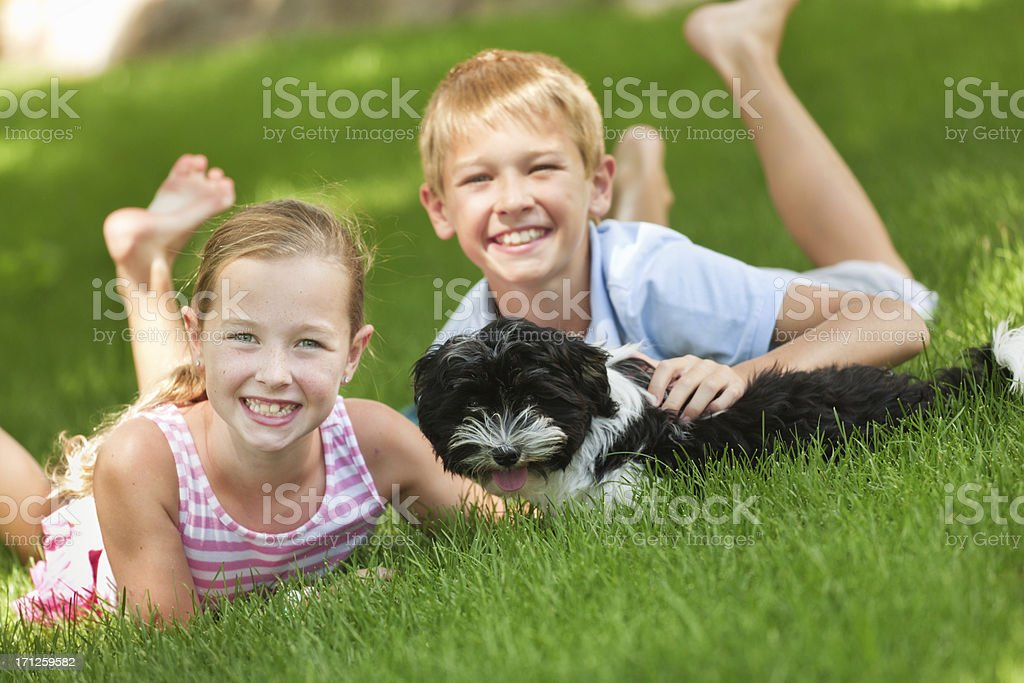 Happy Children Playing with Family Pet Dog in Backyard royalty-free stock photo