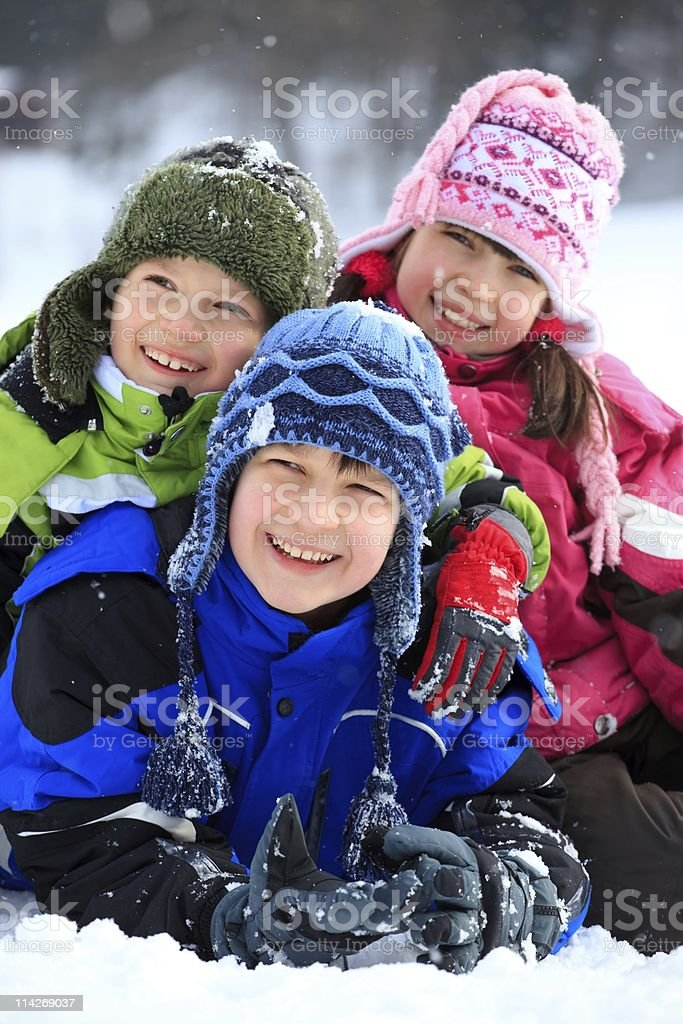 Happy children posing for a picture in the snowfall stock photo