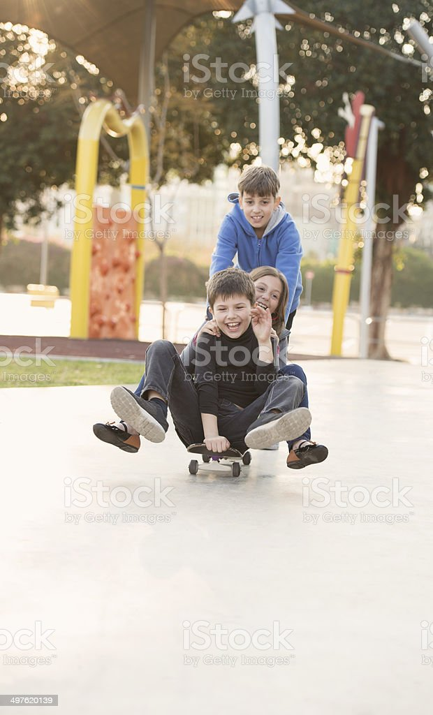 Happy children riding together on skate. royalty-free stock photo