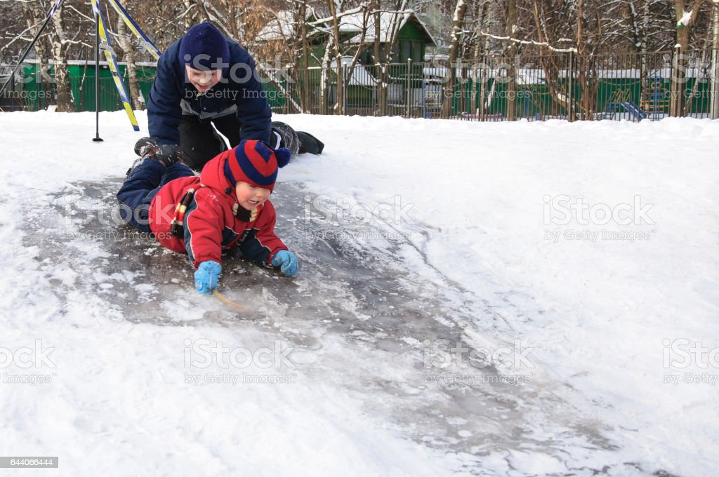 Happy children sliding from a little snowy hill. stock photo