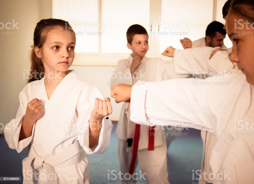 Happy children sparring in pairs in karate class stock photo