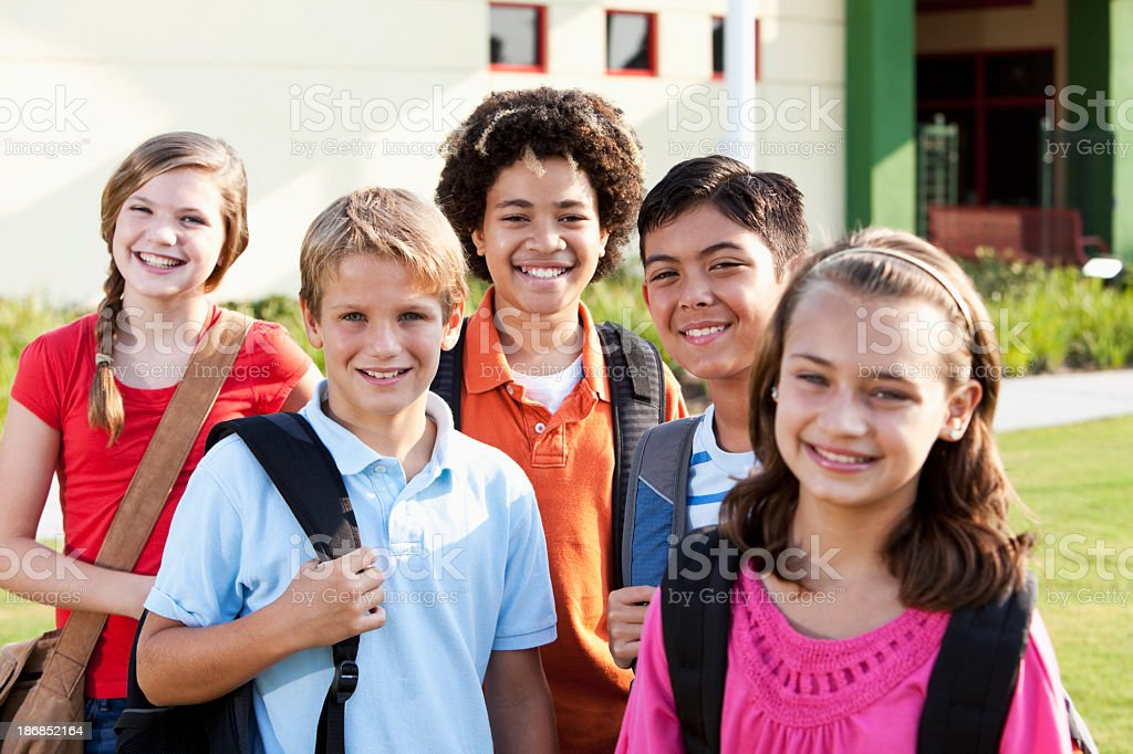 Happy children standing outside school with bookbags stock photo