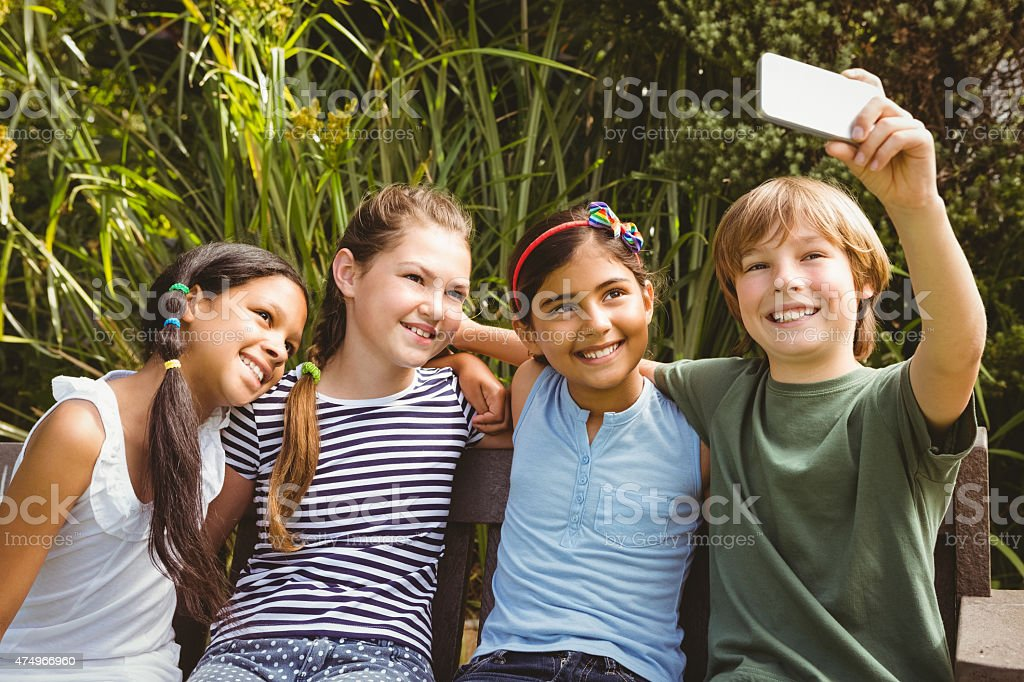 Happy children taking selfie at park stock photo