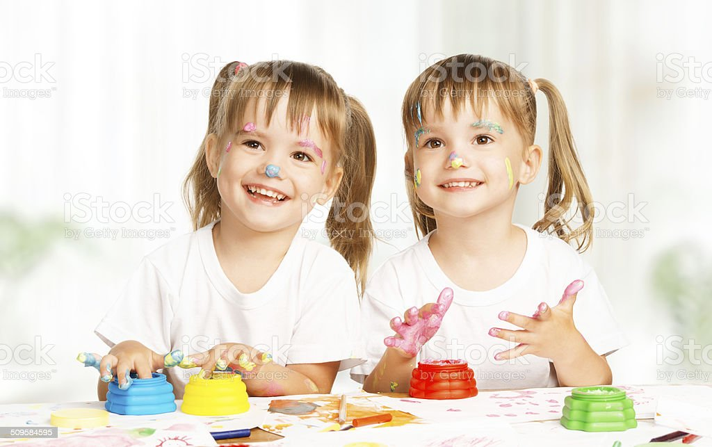 happy children twins draws paints , get dirty stock photo