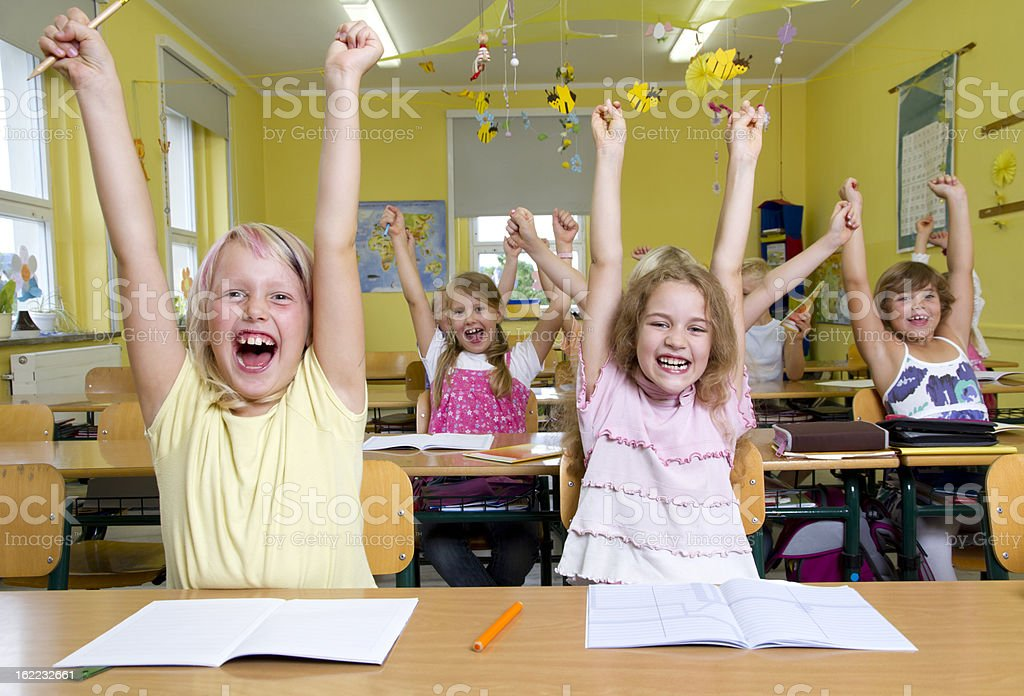Happy children with arms raised at school royalty-free stock photo