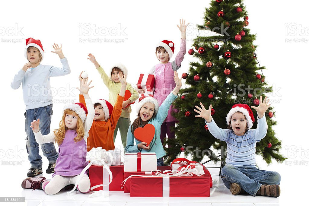 Happy children with raised hands sitting next to Christmas tree. royalty-free stock photo