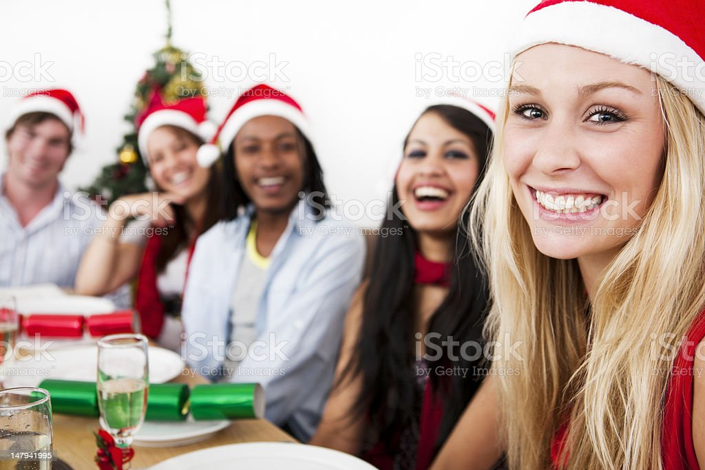 Happy Christmas dinner scene with young adult guests royalty-free stock photo