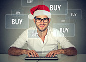 Happy christmas man in santa claus hat buying stuff online