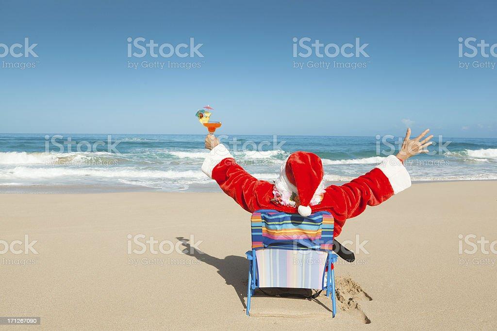 Happy Christmas Santa with Drink Enjoying Hawaiian Tropical Beach Vacation royalty-free stock photo