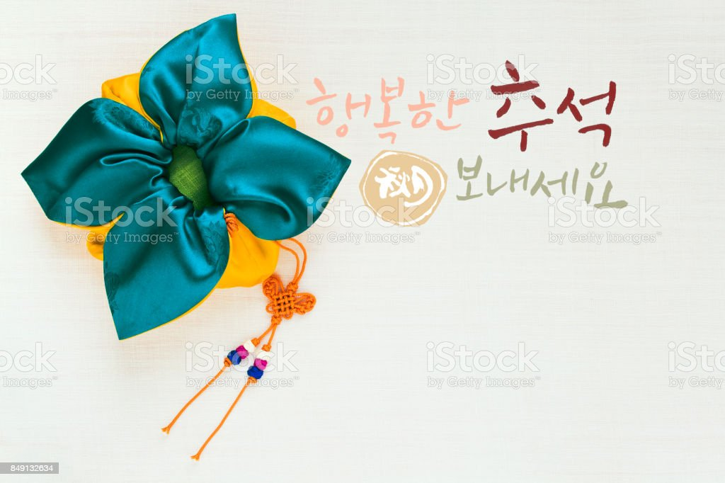 'Happy Chuseok & Hangawi, Translation of Korean Text : Happy Korean Thanksgiving Day' calligraphy and Korean traditional bag & knot background of white ramie fabric. stock photo