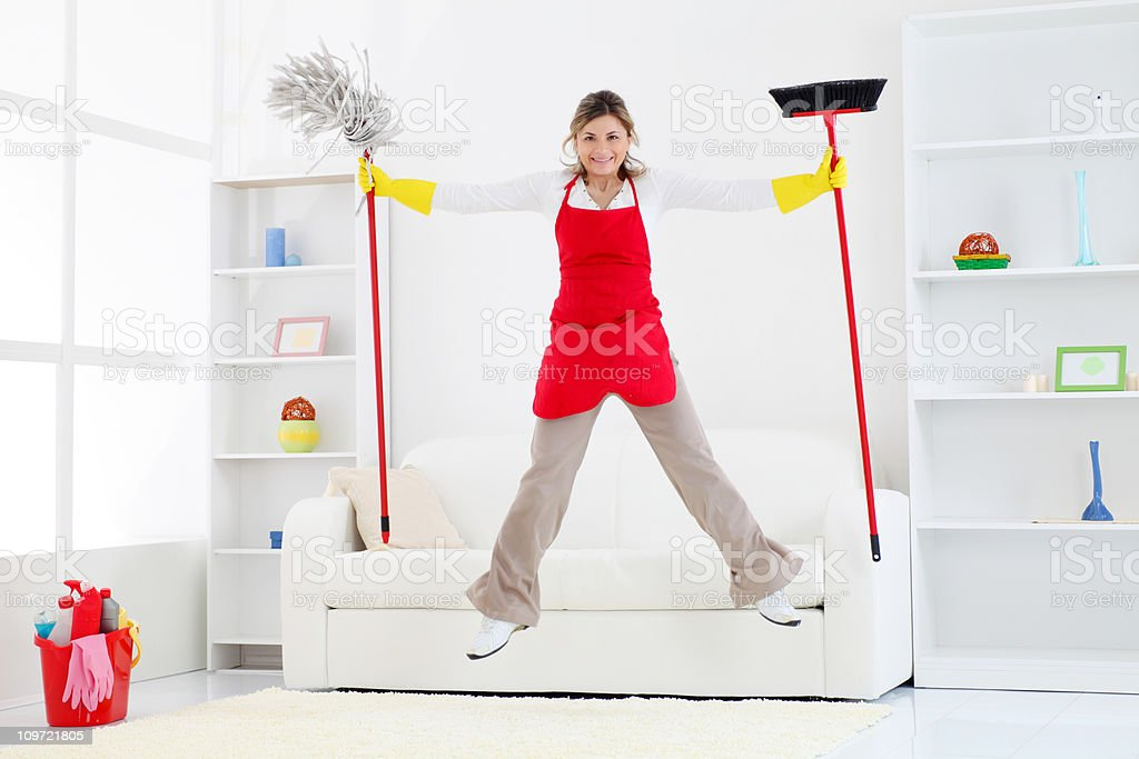 Happy cleaning lady jumping with broom and mop. stock photo