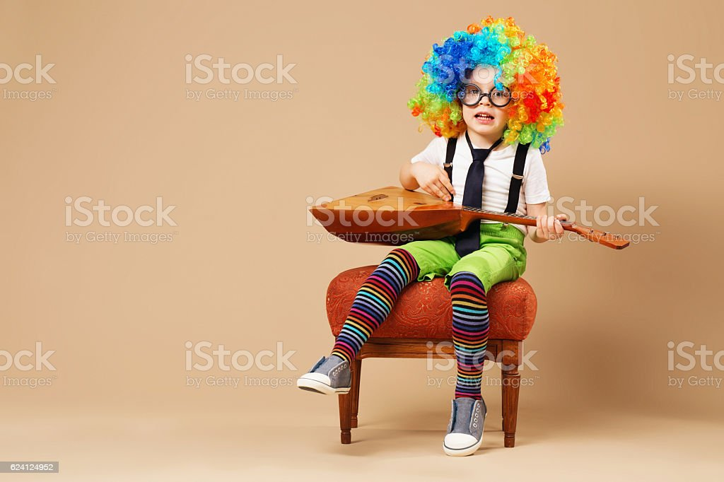 Happy clown boy in large neon colored wig p stock photo
