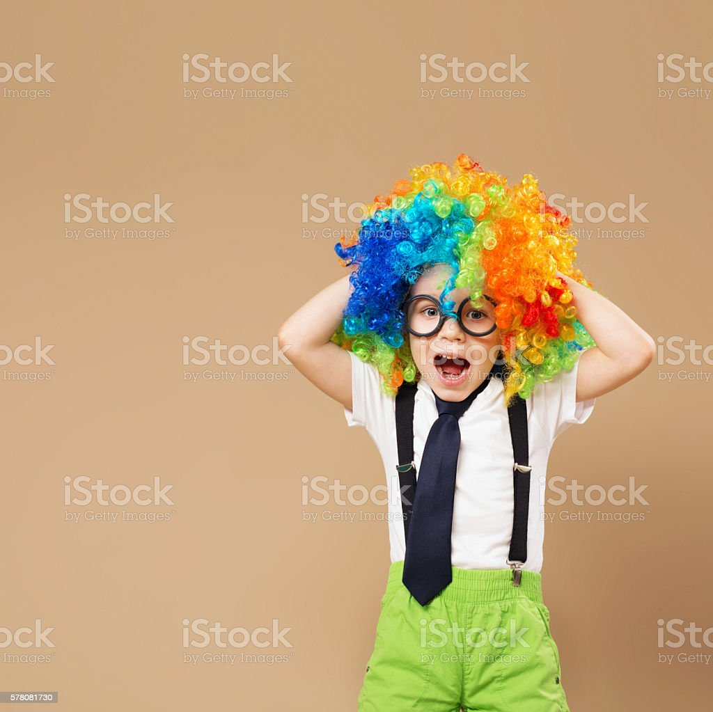 Happy clown boy with large colorful wig. stock photo
