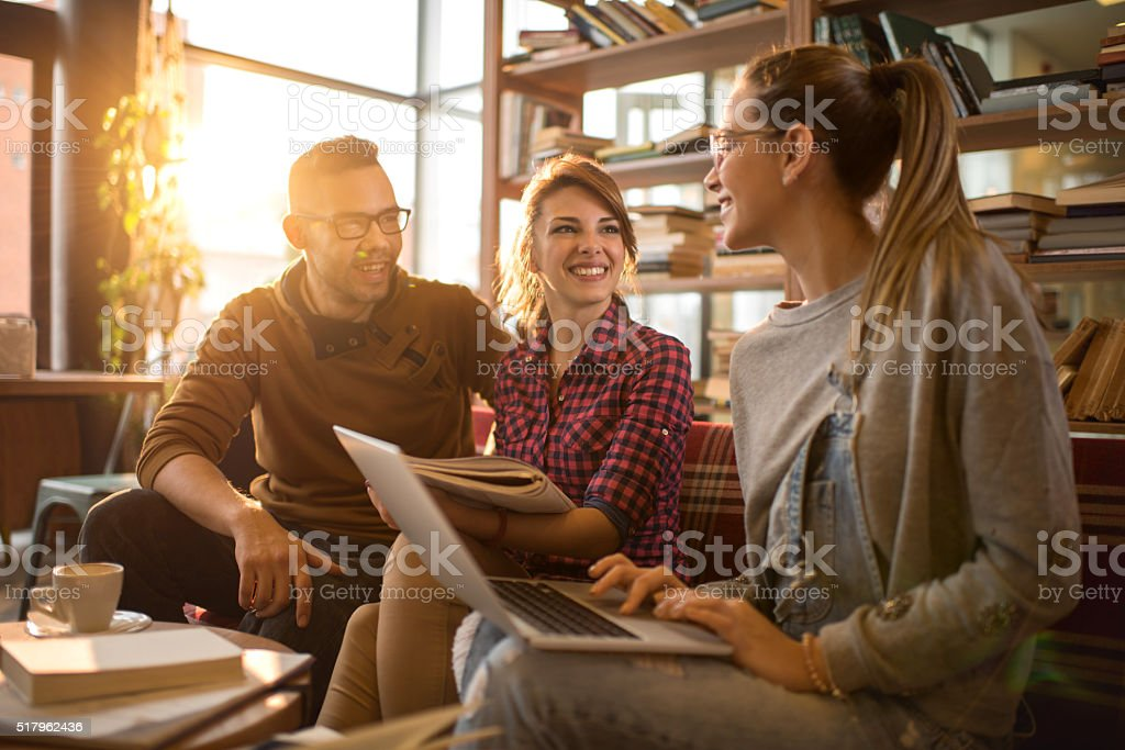 Happy college friends communicating while learning together in library. stock photo