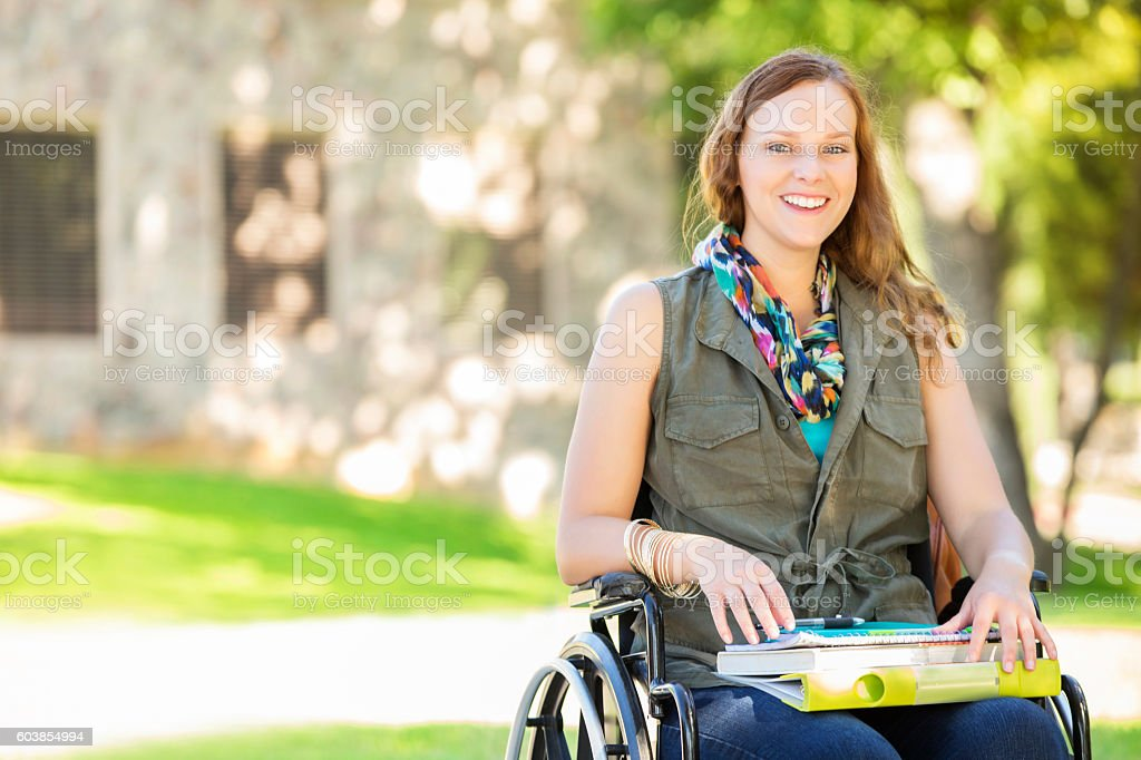 Happy college girl in wheelchair on campus stock photo