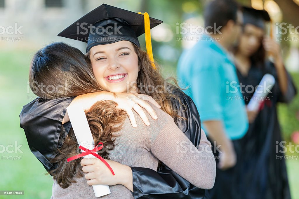 Happy college grad hugs her mom stock photo