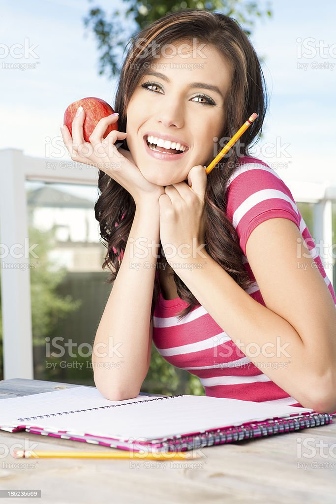 Happy college student holding an apple royalty-free stock photo