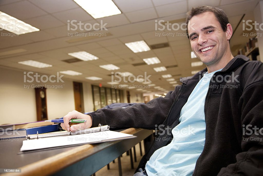 Happy College Student Sitting in Library from Low Angle View royalty-free stock photo