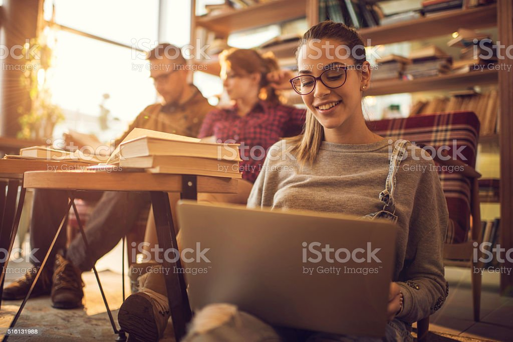 Happy college student surfing the Internet on her laptop. stock photo