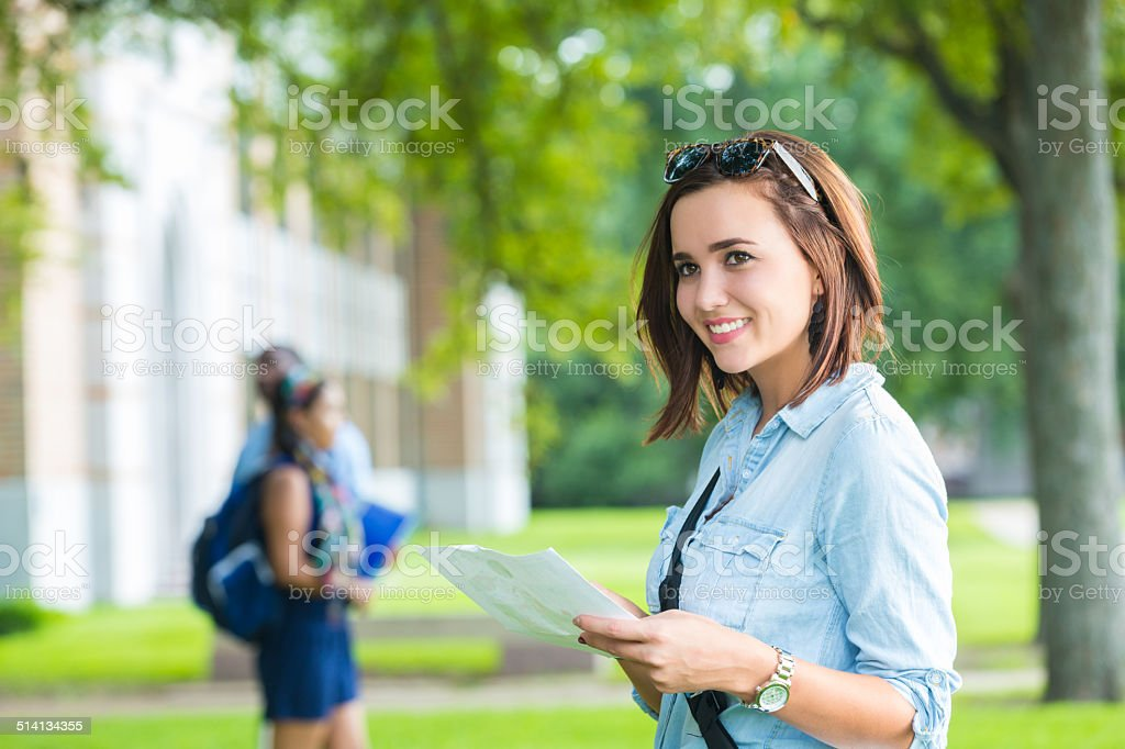 Happy college student using campus man while walking to class stock photo