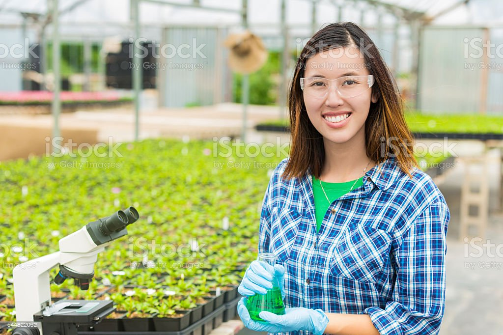 Happy college student working in a greenhouse laboratory stock photo