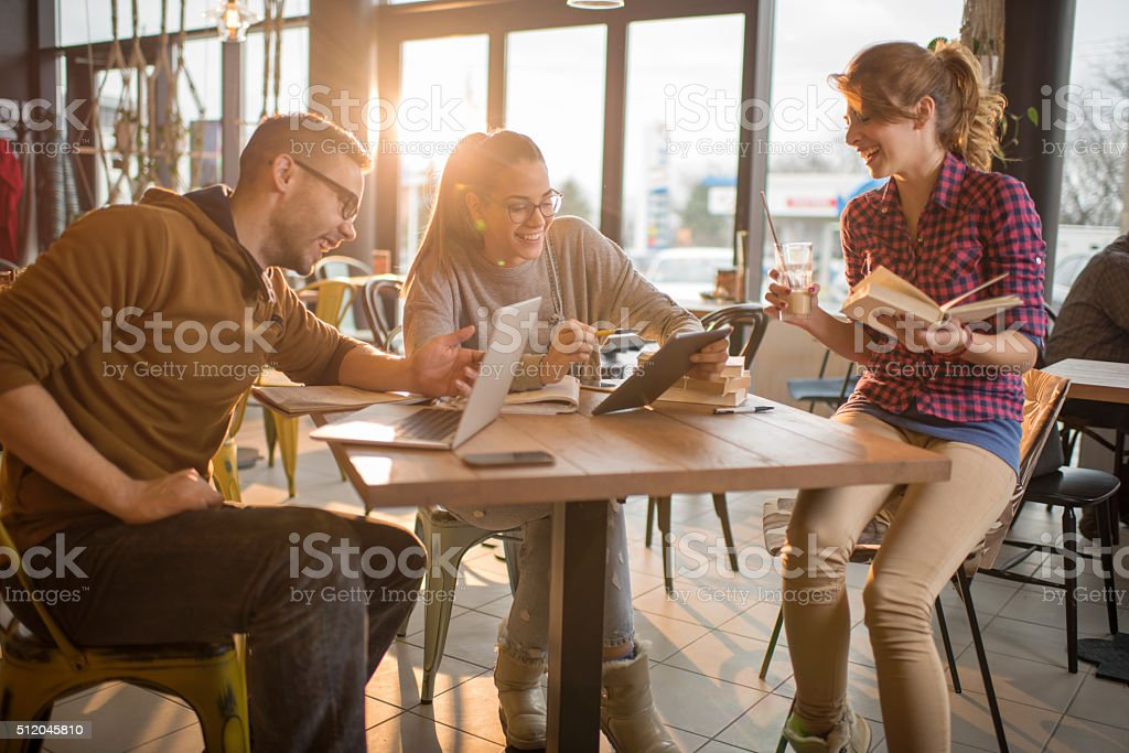 Happy college students cooperating while using digital tablet at cafe. stock photo