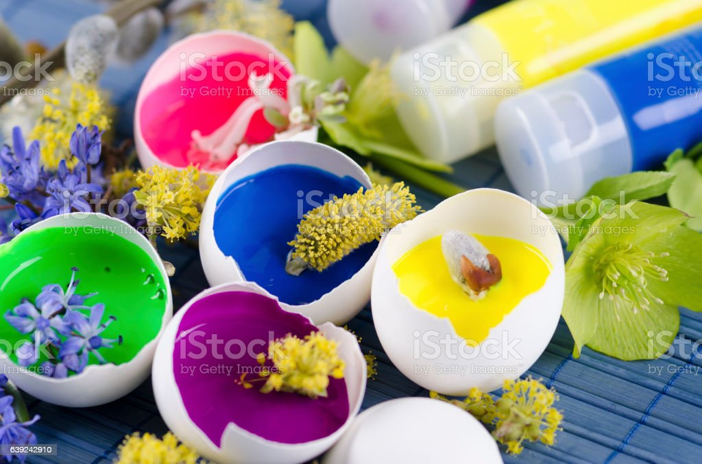Happy colorful Easter decoration with egg shells filled with paints stock photo
