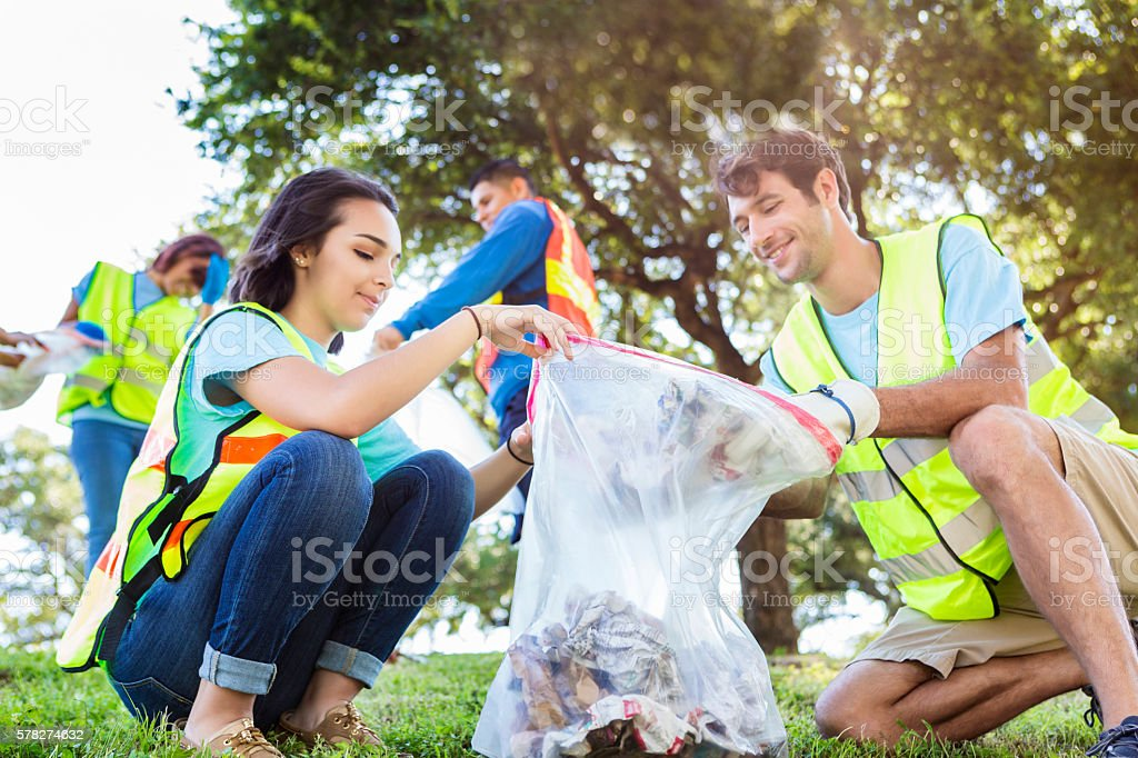 Happy community service people cleaning up the park stock photo