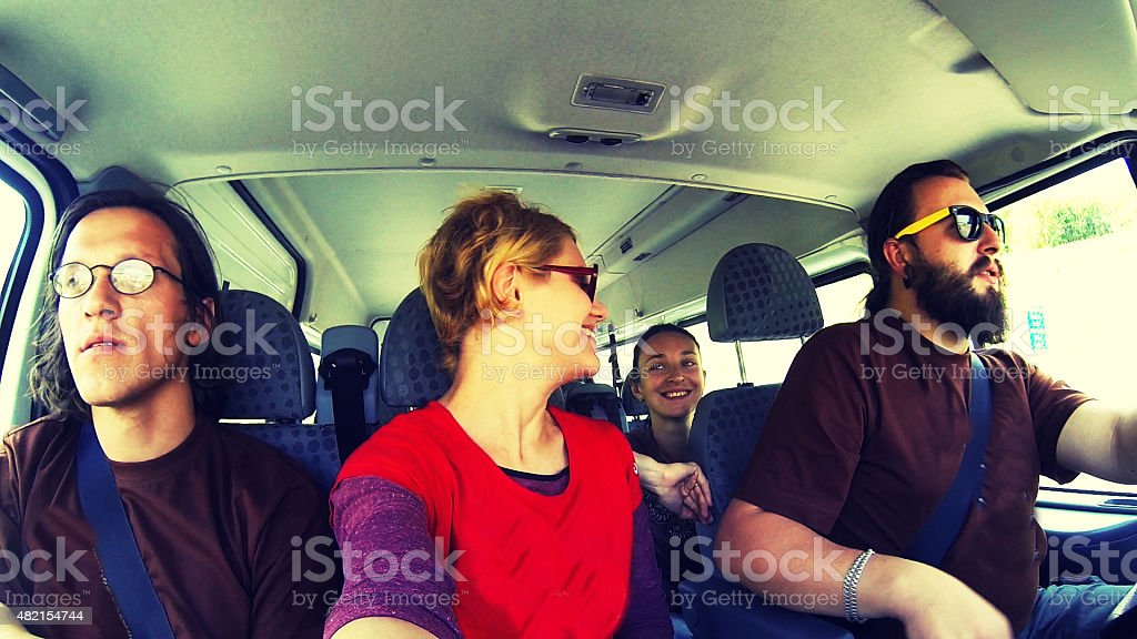 happy company in the car travelling stock photo