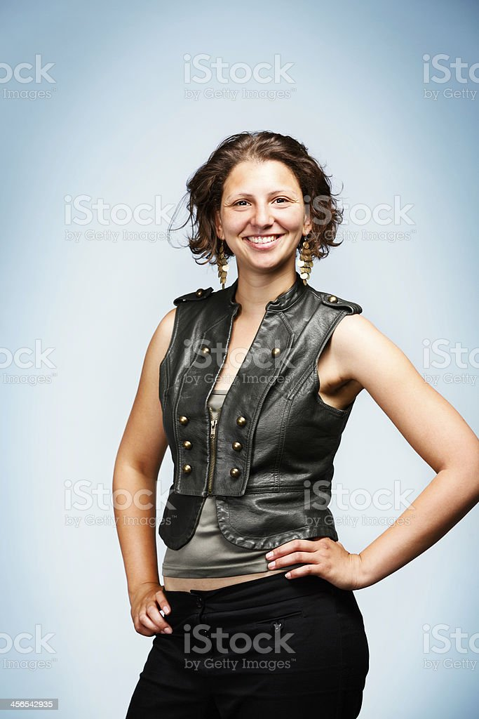Happy, confident brunette smiles, hand on hip stock photo