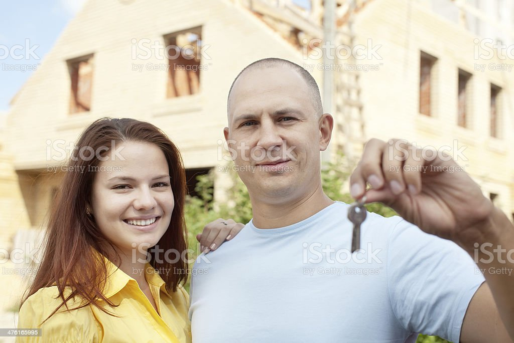 Happy couple against building new house royalty-free stock photo