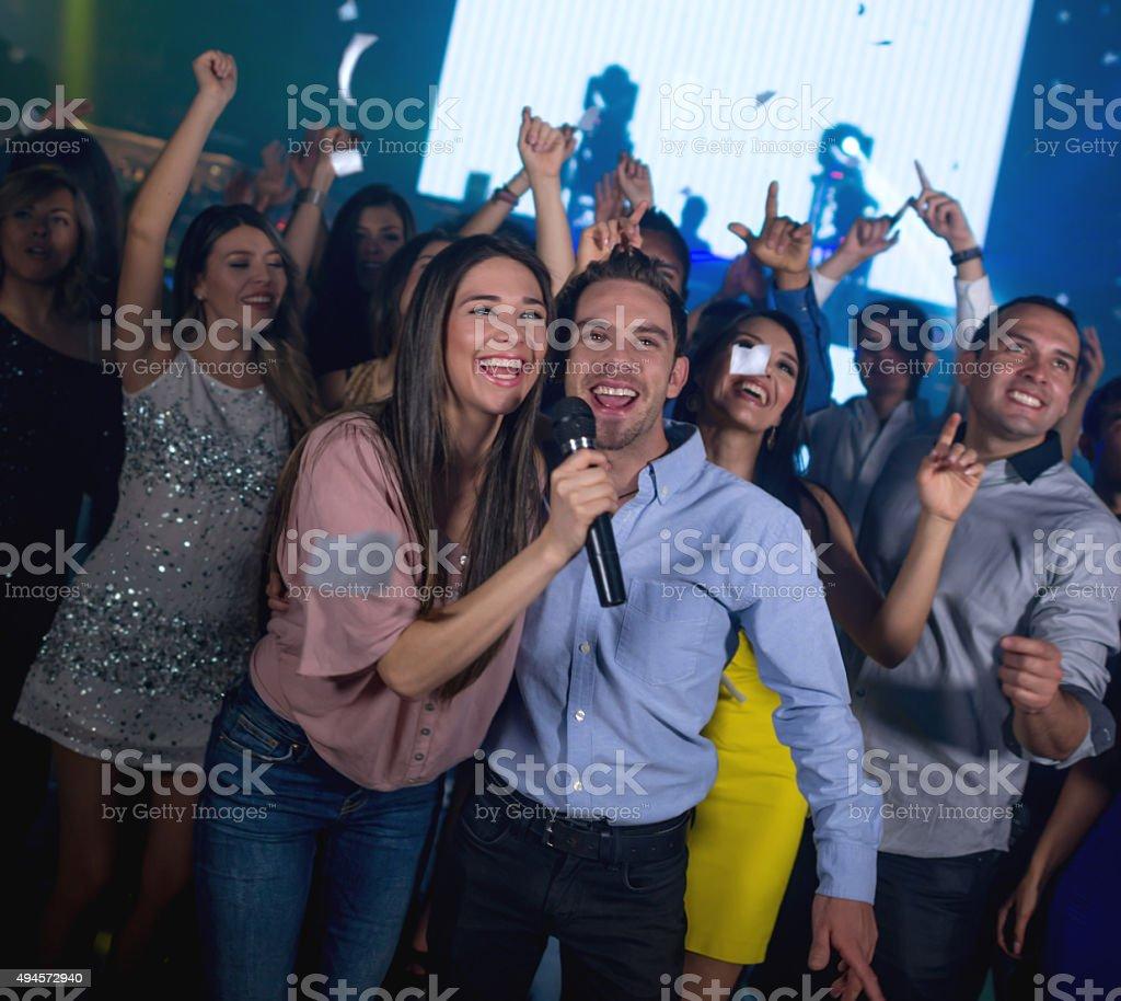 Happy couple at a karaoke party stock photo