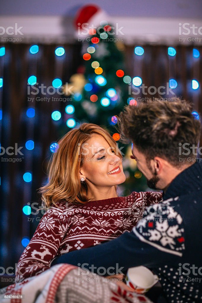 Happy couple at home with christmas tree stock photo
