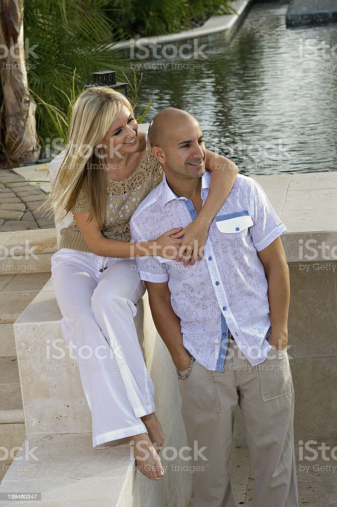 Happy couple by the pool stock photo