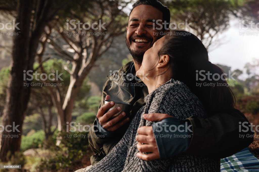 Happy couple camping in forest and having coffee stock photo