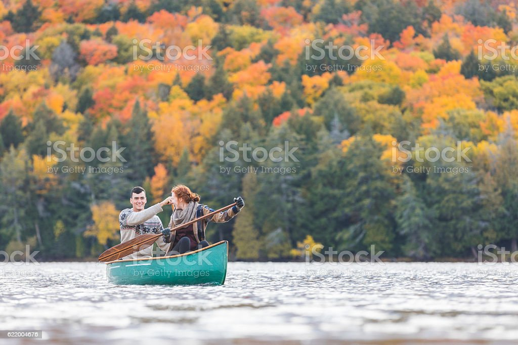 Happy couple canoeing in a lake in Canada stock photo