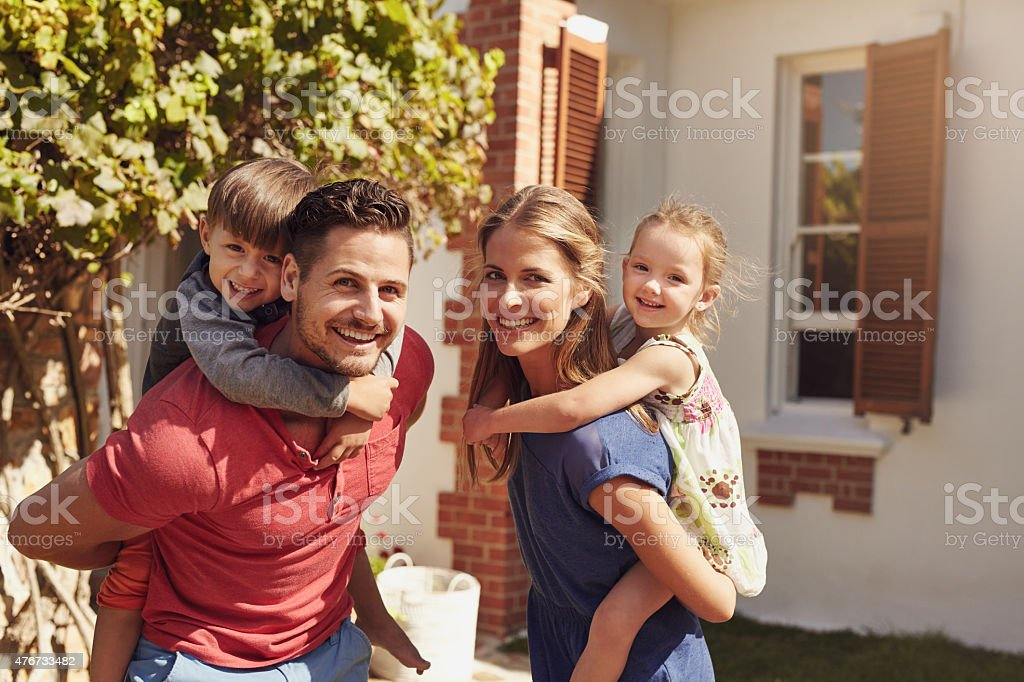 Happy couple carrying children on their backs stock photo