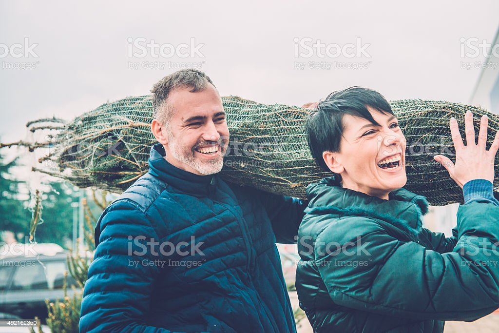 Happy Couple Carrying Christmas Tree on Shoulders, Europe stock photo