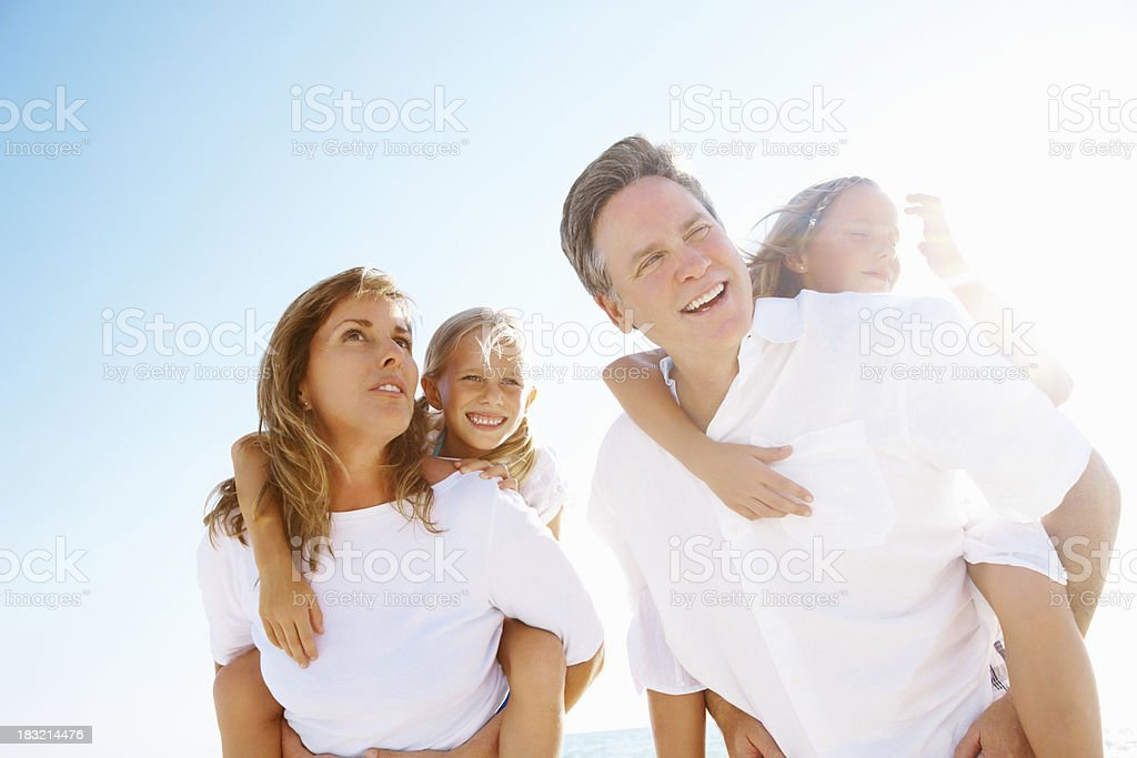Happy couple carrying their children on back against sky royalty-free stock photo
