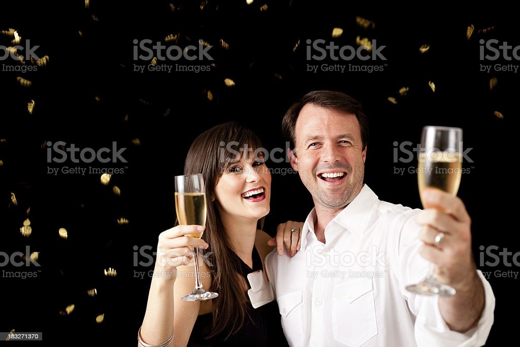 Happy Couple Cheering and Celebrating New Year with Champagne Flutes royalty-free stock photo