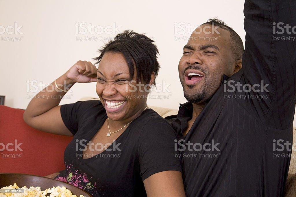 Happy Couple Cheering at the TV royalty-free stock photo