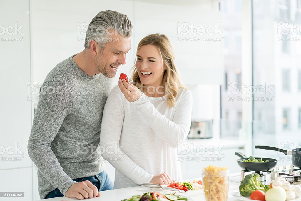 Happy couple cooking at home stock photo