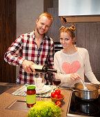 Happy couple cooking pasta