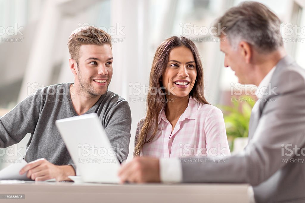 Happy couple cooperating with financial advisor in the office. stock photo