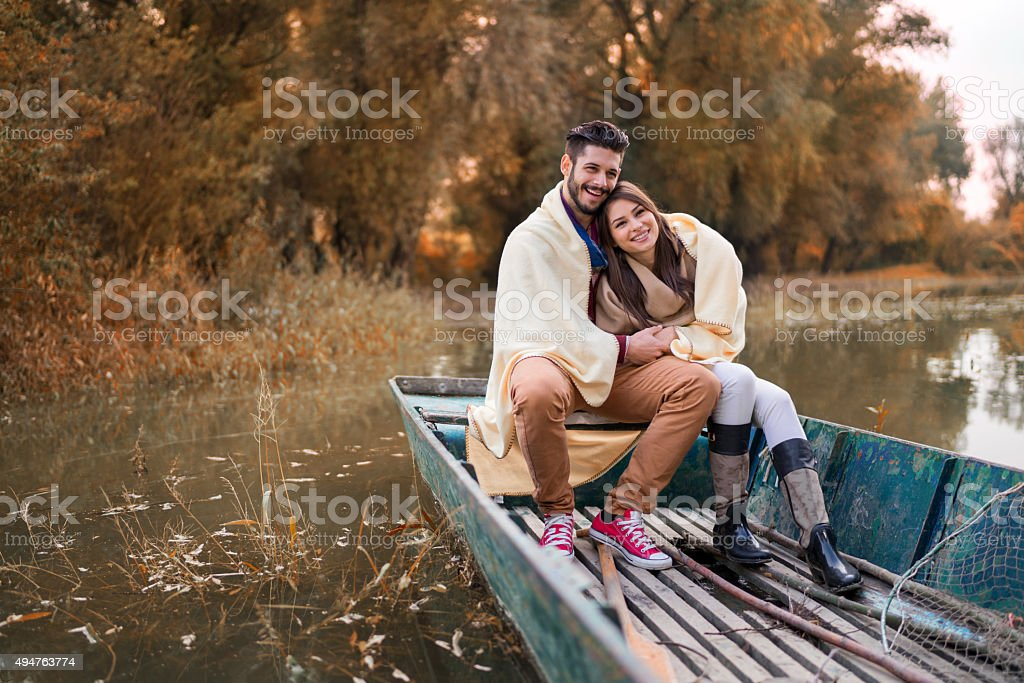 Happy couple covered with blanket enjoying in a boat. stock photo