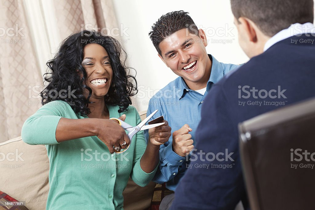Happy couple cutting up credit card with financial advisor stock photo