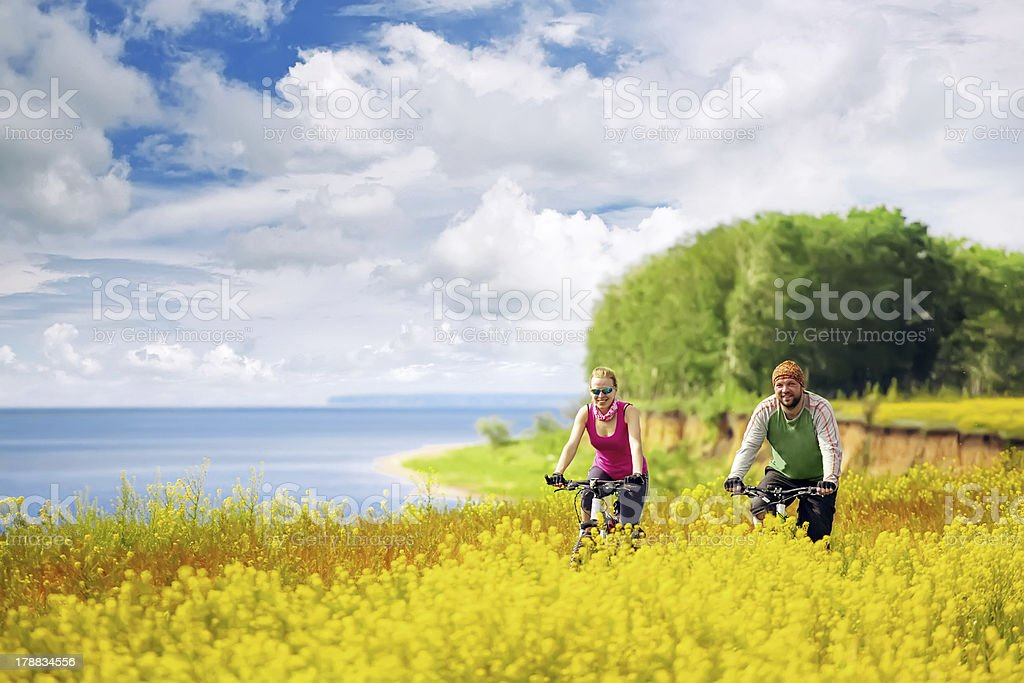 happy couple cycling in canola fields royalty-free stock photo