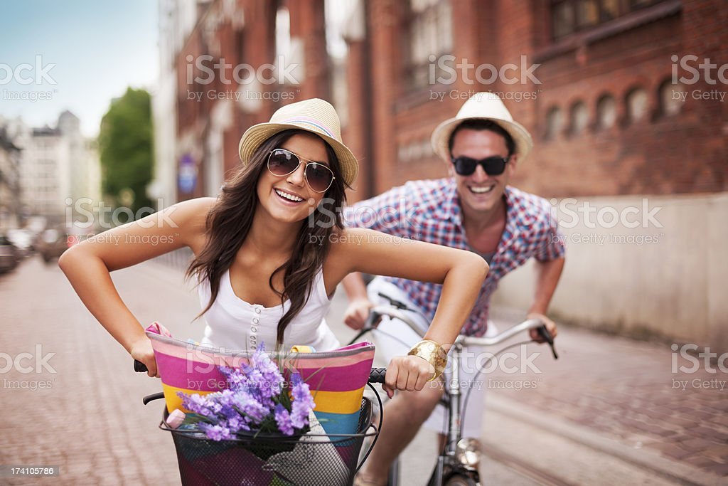 Happy couple cycling in the city stock photo