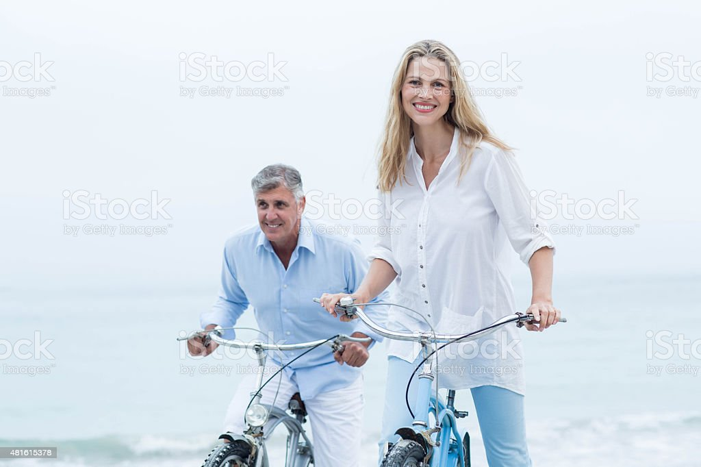 Happy couple cycling together stock photo