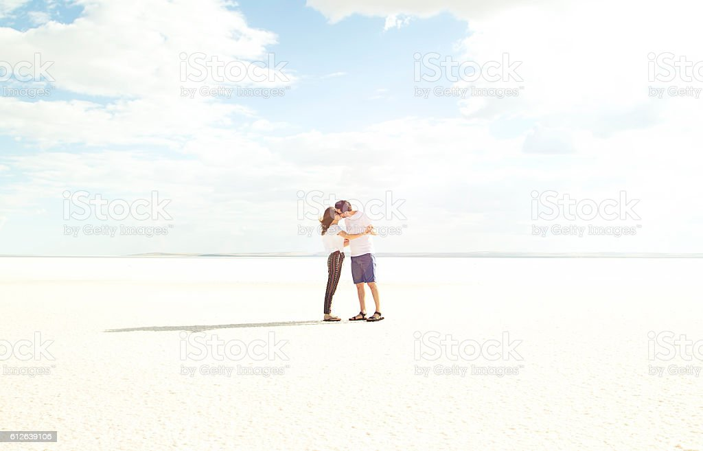 Happy couple dancing and kissing on salt lake stock photo
